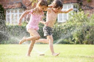 Kids running through sprinklers